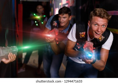 Group portrait of joyful emotional people with laser guns  playing laser tag  game together in dark labyrinth