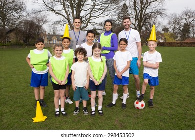 A group portrait of a kids soccer team, behind them are their coaches. They are smiling and two of the boys can be seen holding cones on their head messing amount.