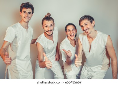 Group Portrait Of Masseurs In Spa Salon. Three white men and one woman looking at camera. Physical Therapists. Beauty Treatment, Massage Therapy. Healthcare, Medicine Concept. Wellness, Lifestyle.