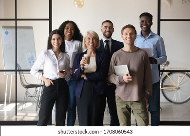 Group portrait of multicultural diverse businesspeople stand together look at camera posing in modern office show unity and support, smiling multiracial colleagues make team picture at workplace