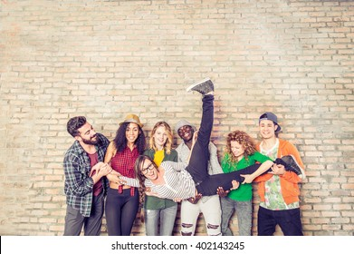 Group portrait of multi-ethnic boys and girls with colorful fashionable clothes holding friend and posing on a brick wall - Urban style people having fun - Concepts about youth  and togetherness