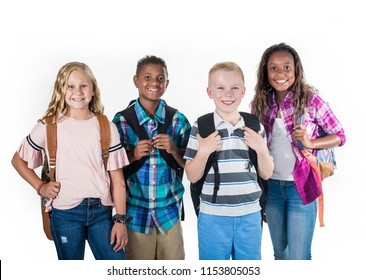 Group portrait of pre-adolescent school kids smiling on a white background. Back to school photo of a diverse group of children wearing backpacks isolated on a white background