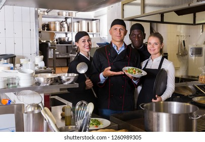 Group portrait of professional chefs posing together in modern kitchen of restaurant