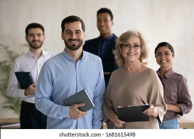 Group portrait of smiling diverse multiethnic businesspeople pose together in office, happy multiracial colleagues coworkers feel motivated successful show team strength and unity, leadership concept
