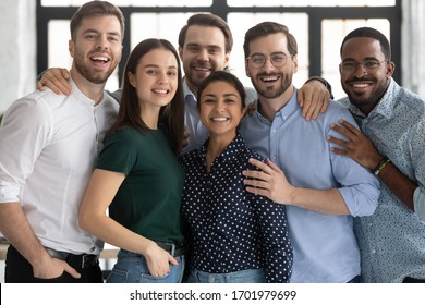 Group portrait of smiling diverse multiracial young businesspeople posing together in office, happy multiethnic millennial colleagues look at camera show unity and support at work, teamwork concept