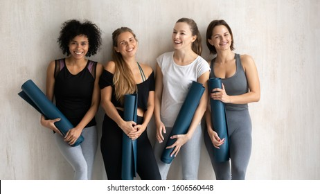 Group portrait smiling diverse women with yoga mats in hands posing at grey fitness center wall background, beautiful sporty girls wearing sportswear looking at camera, having fun after training