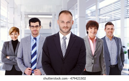 Group portrait of successful, determined business team at office with boss in front. Smiling, standing, looking at camera, wearing suit.