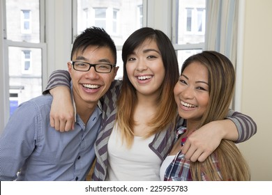 Group portrait of three Asian friends relaxing at home.