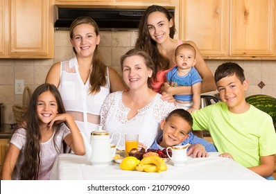 Group portrait three generation happy big family, grandmother, daughters, sons, grandchildren ready to have breakfast in the kitchen of their house on mothers day. Positive face expressions, emotions