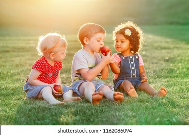 Group portrait of three white Caucasian and latin hispanic children boy and girls sitting together sharing and eating apple food. Love friendship childhood concept. Best friends forever.