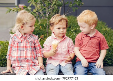 Group portrait of three white Caucasian cute adorable funny children toddlers sitting together sharing ice-cream food. Love friendship jealousy concept. Best friends forever.
