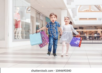 Group portrait of two cute adorable preschool children going shopping. Caucasian little girl and boy running in mall. Kids holding shopping bags.