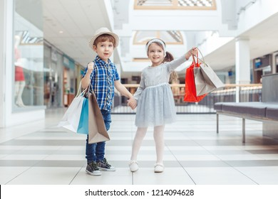Group portrait of two cute adorable preschool children going shopping. Caucasian little girl and boy running in mall. Kids holding shopping bags. Black Friday sale concept.
