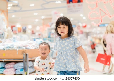 Group portrait of two cute adorable sibling preschool children going shopping in Supermarket.Asian Sister and brother running in mall in Mid year sale season.