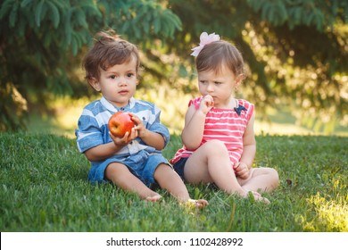 Group portrait of two white Caucasian cute adorable funny children toddlers sitting together sharing apple food. Envy friendship childhood concept. Best friends forever boy and girl
