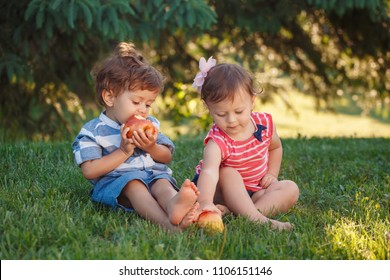Group portrait of two white Caucasian cute adorable funny children toddlers sitting together sharing apple food. Friendship childhood concept. Best friends forever boy and girl