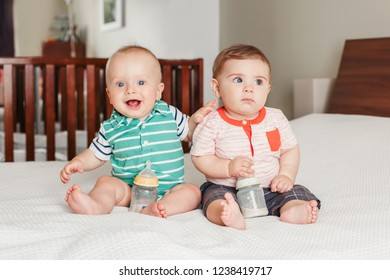 Group portrait of two white Caucasian cute adorable funny baby boys sitting together on bed socializing. Friendship childhood concept. Best friends forever. Pessimistic and optimistic tempers