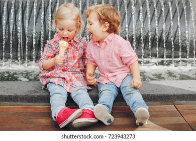 Group portrait of two white Caucasian cute adorable funny children toddlers sitting together sharing ice-cream food. Love friendship concept. Best friends forever.