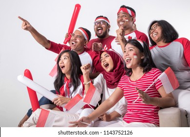 group portrait of young indonesian supporter people watching soccer match with excitement