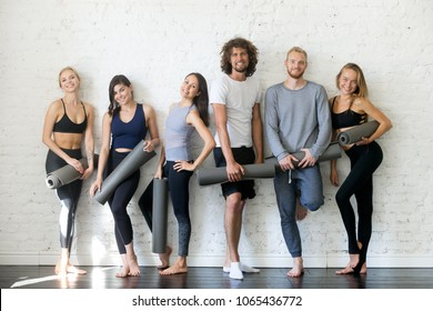 Group portrait of young sporty people looking at camera. Candid students taking rest after fitness activity, time to recover strength, Fitness or yoga instructors friendly smiling, inviting for lesson