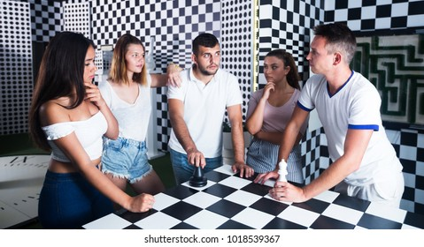 Group of positive adults standing near chessboard in quest room and solving conundrum