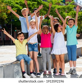 Group of positive children holding hands up and smiling together in park