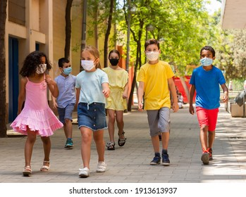 Group of positive children in masks walking together on the street