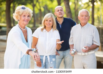 Group of positive mature people playing petanque  outdoor