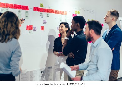 Group of positive multicultural students standing near wall with colorful stickers and discussing text notes written on papers during brainstorming meeting.Team of employees collaborating in office