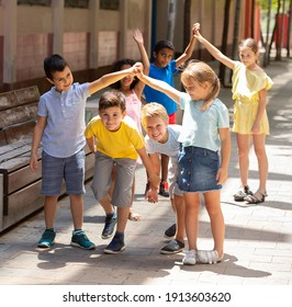 Group of positive schoolchildren holding hands up and playing together in park
