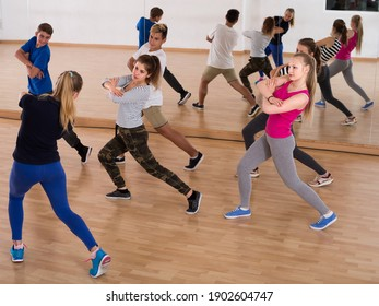 Group of positive smiling germany teenagers dancing in classroom