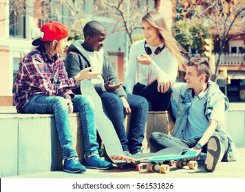 Group of  positive smiling teenage friends relaxing and chatting in town square