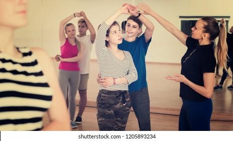 Group of positive spanish teen dancing salsa in dance studio