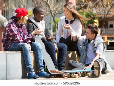 Group of positive teenage friends relaxing and chatting in town square