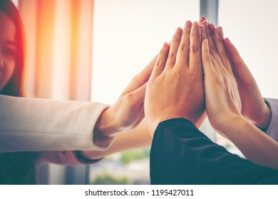 Group of powerful diversity creative people high five on air to greeting power of team. Multiethnic businesspeople working together. Collaboration in Business Team success. StrongTeamwork concept.