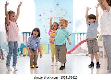 Group of preschool children doing gymnastics in kindergarten. Physical activity for kids in playschool