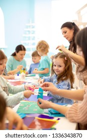 Group of preschool children drawing with pencils and gluing with glue stick on art class in kindergarten or daycare centre
