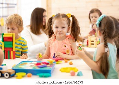 Group of preschool children playing with colorful didactic toys at kindergarten