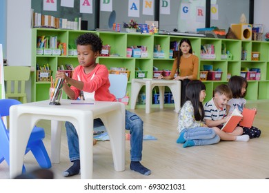 group of preschool kids in attention of playing and learning in classroom with teacher watching closely in background, all enjoy learning together