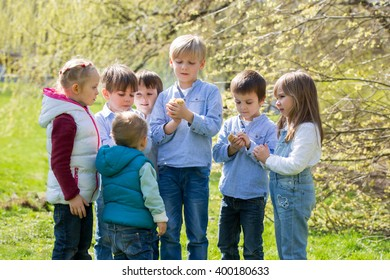 Group of preschool kids, friends and siblings, playing in the park with little chicks, springtime during the day