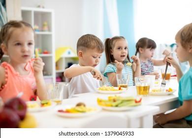 Group of preschool kids have a lunch in daycare. Children eat healthy food in kindergarten