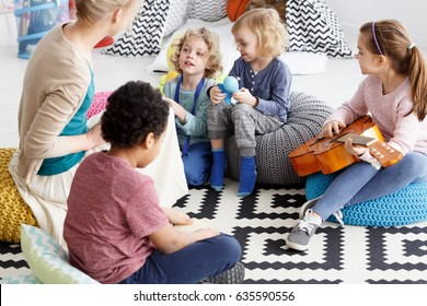 Group of preschool kids sitting on a carpet in kindergarten