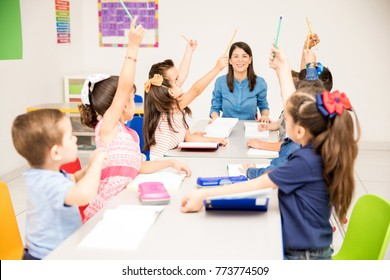 Group of preschool students raising their hands during class and trying to participate