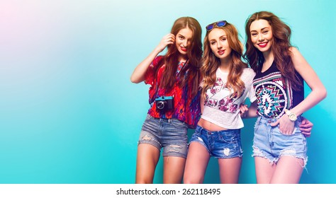 Group of pretty young girls in stylish clothes posing in studio against blue background. Three pretty  woman smiling  and wolfing together. sunny summer colors.