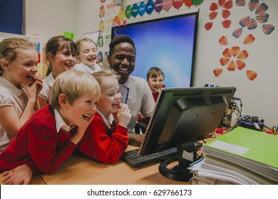 Group of primary school students are crowded round a computer with their teacher. They are all laughing and looking at the computer screen.
