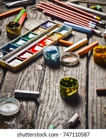A group of products for drawing and creativity on a wooden table. Rustic style. Gouache, oil painting, watercolor paints, crayons, pencils.