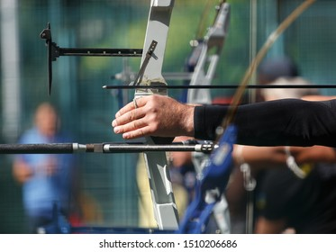 Group of professional archers shooting targets with modern longbows.Focus on athlete holding bow with arrow.Archer competition outdoor