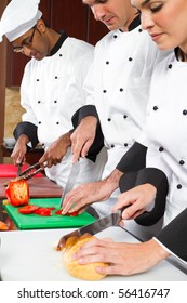 group of professional chefs cooking in commercial kitchen