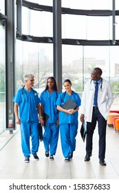 group of professional health care workers walking in hospital