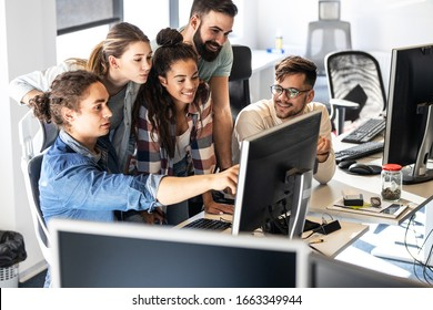 Group of programmers discussing about new project.They looking at the computer screen and testing the code.Developing new software.